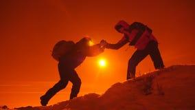 Туристский помогая подъем товарища по команде, человек с рюкзаком достиг вне руку помощи к его другу Принципиальная схема сыгранн видеоматериал