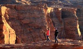 Туристы стоя на краю скал на загибе подковы стоковые фотографии rf
