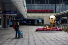 Турист ждет друзей на здании порта Zhuhai стоковое фото rf