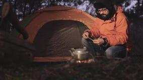 Турист на сумраке на предпосылке его шатра разжигает огонь в лесе для того чтобы греть воду в чайнике _ акции видеоматериалы