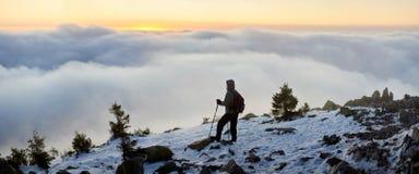 Турист с рюкзаком на скалистом горном пике на предпосылке туманной долины и голубого неба на восходе солнца стоковое фото rf