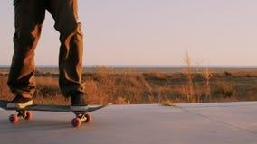 Тысячелетние езды скейтбордиста хипстера в заходе солнца видеоматериал