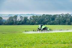 Трактор во всходах поля молодых брызгает стоковое фото rf