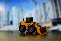 Трактор игрушки на строительной площадке стоковое фото