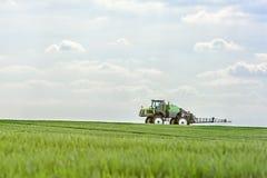 Трактор удабривает всходы пшеницы стоковое фото