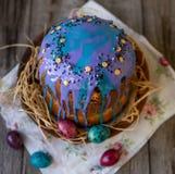 Традиционно испеченные правоверные торты пасхи с glace замороженностью и яркий меньшие яйца на деревянной предпосылке с тканью шн стоковые изображения