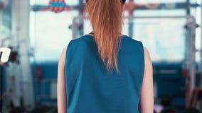 Тренировка девушки вида сзади задняя молодая атлетическая с гантелями сток-видео