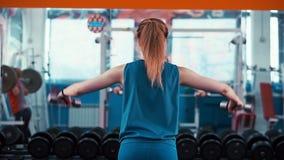 Тренировка девушки вида сзади задняя молодая атлетическая с гантелями видеоматериал
