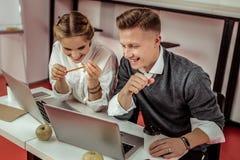 Товарищи по работе находясь в большем настроении пока работающ совместно стоковые фото
