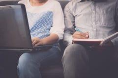 Товарищ по работе человека и женщины работая на ноутбуке и блокноте в офисе стоковые фото