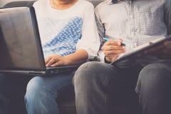 Товарищ по работе человека и женщины обсуждая совместно пока использующ ноутбук в офисе стоковые изображения
