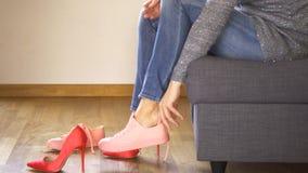 Тонкая женщина в джинсах на кресле принимает сексуальные красные пятки и кладет на тапки коралла акции видеоматериалы