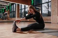 Тонкая девушка одетая в черном sportswear делает протягивать на циновке фитнеса в современном спортзале с деревянным украшением стоковые изображения