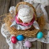 Торт пасхи - kulich Традиционный хлеб пасхи сладкий украсил белую замороженность в корзине соломы и покрашенные яйца на салфетке  стоковое фото