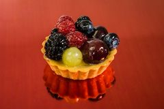 Торт со свежими био плодами, виноградинами, полениками, ежевиками, фото взгляда со стороны, предпосылкой зеркала красной стоковое изображение