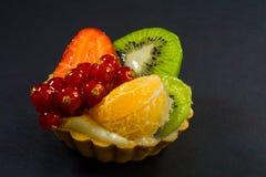 Торт со свежим био плодом, апельсином, кивиом, красной смородиной, клубникой, фото взгляда со стороны, черной предпосылкой стоковое изображение