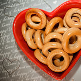 Тop view. Bagels on red plate in shape of heart on gray background. royalty free stock image