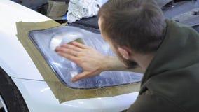 Фара полируя, обработка светов автомобиля Работник обслуживания автомобиля полирует фару пассажирского автомобиля акции видеоматериалы