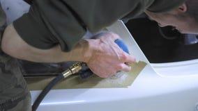 Фара полируя, обработка светов автомобиля Работник обслуживания автомобиля полирует фару пассажирского автомобиля с a сток-видео