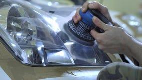 Фара полируя, обработка светов автомобиля Работник обслуживания автомобиля полирует фару пассажирского автомобиля с a акции видеоматериалы