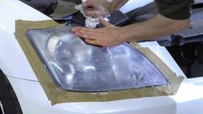 Фара полируя, обработка светов автомобиля Работник обслуживания автомобиля полирует фару пассажирского автомобиля сток-видео