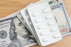 Фармация, здравоохранение или медицинская стоить концепция, белый пакет таблеток капсулы на куче банкнот денег доллара США, пацие стоковое изображение rf