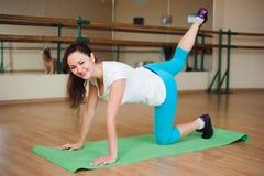 Фитнес, спорт, работая образ жизни - счастливую женскую одежду в bodysuits делая тренировки на спортзале стоковые изображения rf