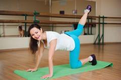 Фитнес, спорт, работая образ жизни - счастливую женскую одежду в bodysuits делая тренировки на спортзале стоковые фото