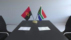 Флаги Анголы и Южной Африки и бумаги на таблице Переговоры и подписание международного соглашения иллюстрация штока