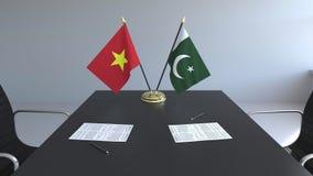 Флаги Вьетнама и Пакистана и бумаги на таблице Переговоры и подписание международного соглашения схематическо иллюстрация штока