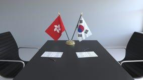 Флаги Гонконга и Южной Кореи и бумаги на таблице Переговоры и подписание международного соглашения бесплатная иллюстрация