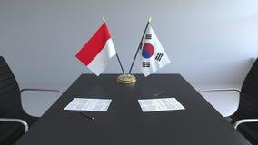 Флаги Индонезии и Южной Кореи и бумаги на таблице Переговоры и подписание международного соглашения иллюстрация штока