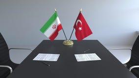 Флаги Ирана и Турции и бумаги на таблице Переговоры и подписание международного соглашения Схематическое 3D иллюстрация штока