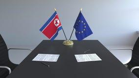 Флаги Корейской Северной Кореи и Европейского союза и бумаг на таблице Переговоры и подписание международного соглашения бесплатная иллюстрация