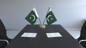 Флаги Пакистана и бумаг на таблице Переговоры и подписание согласования схематический перевод 3d иллюстрация штока