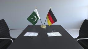 Флаги Пакистана и Германии и бумаги на таблице Переговоры и подписание международного соглашения схематическо бесплатная иллюстрация