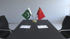 Флаги Пакистана и Китая и бумаги на таблице Переговоры и подписание международного соглашения Схематическое 3D бесплатная иллюстрация