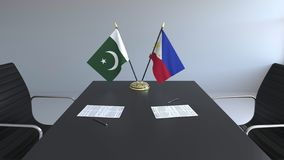 Флаги Пакистана и Филиппин и бумаги на таблице Переговоры и подписание международного соглашения иллюстрация вектора