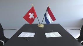 Флаги Швейцарии и Нидерланд и бумаги на таблице Переговоры и подписание международного соглашения иллюстрация вектора