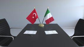 Флаги Турции и Италии и бумаги на таблице Переговоры и подписание международного соглашения Схематическое 3D иллюстрация штока