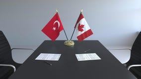 Флаги Турции и Канады и бумаги на таблице Переговоры и подписание международного соглашения Схематическое 3D иллюстрация штока