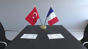 Флаги Турции и Франции и бумаги на таблице Переговоры и подписание международного соглашения Схематическое 3D иллюстрация штока