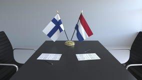 Флаги Финляндии и Нидерланд и бумаги на таблице Переговоры и подписание международного соглашения иллюстрация вектора