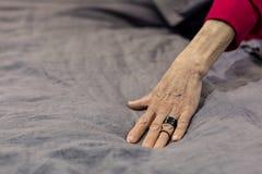 Фотография старея руки сударыни на серый покрывать кровати стоковые изображения rf