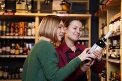 Фото 2 женщин с бутылкой вина стоковые изображения rf