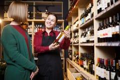 Фото 2 женщин с бутылкой вина в руке стоковые изображения rf