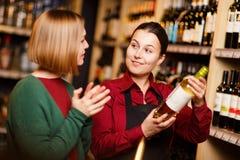 Фото 2 молодых женщин с бутылкой в руках на винном магазине стоковое фото