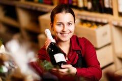 Фото молодой женщины с бутылкой в руках в винном магазине стоковые фото