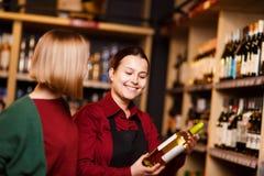 Фото на стороне 2 усмехаясь женщин с бутылкой вина в магазине на предпосылке полок стоковые фотографии rf