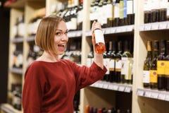 Фото счастливой женщины с бутылкой вина на запачканной предпосылке полок с бутылками стоковое фото rf